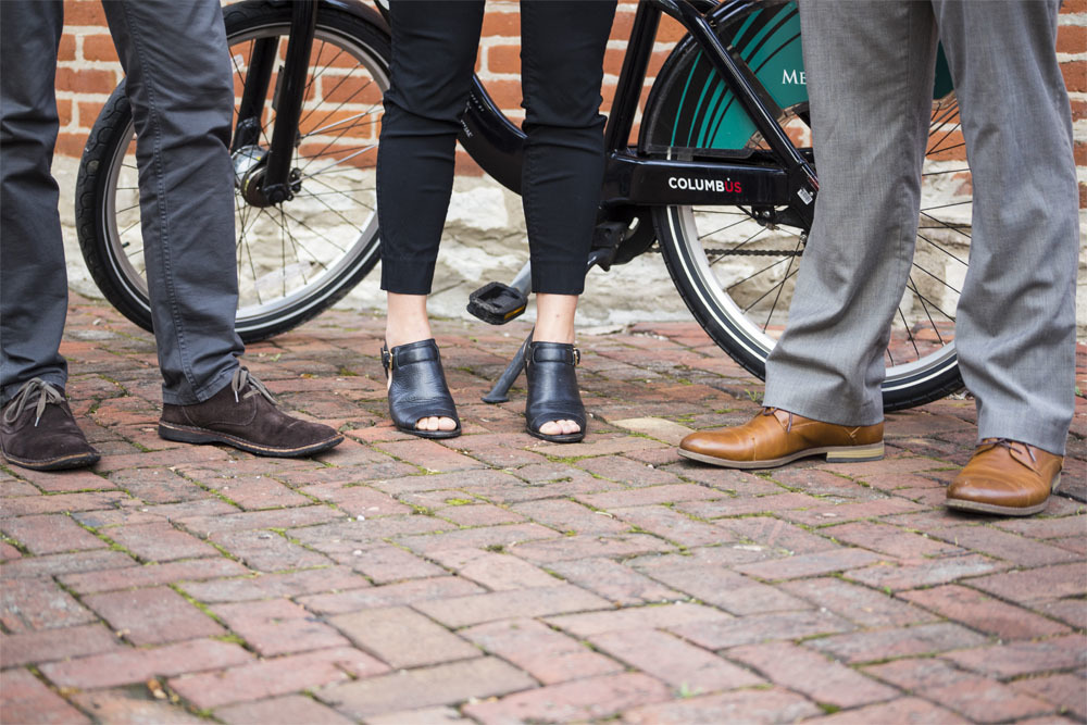 3 Riders Showing Off Their Shoes In Front Of Bike