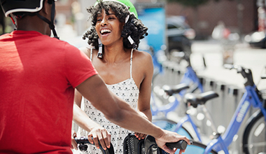 Guy and Girl Laughing Helmets with Citi Bikes